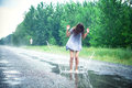 Girl in a puddle beautiful jumps on the road Stock Photo
