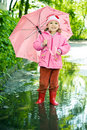 Girl in the puddle with umbrella Stock Photo