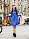 Girl with purchases during the christmas sales smiling at street Royalty Free Stock Photos