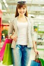 Girl with purchases vertical shot of a happy carrying her after shopping Royalty Free Stock Image