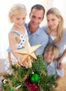 The girl put the Christmas star on top of the tree Royalty Free Stock Photography