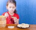Girl puts honey on the spoon cookies Royalty Free Stock Photo