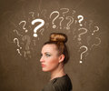 Girl with question mark symbols around her head teenage Royalty Free Stock Photos