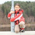 Girl on railing of dam smiling kid in red winter jacket kneeing concrete and holding a lamp Royalty Free Stock Photography