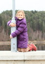 Girl on railing of dam smiling kid in winter clothes kneeing concrete and holding a lamp Royalty Free Stock Photography