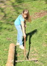 Girl with rake little in blue pants and t shirt standing and raking wooden green grass Stock Images