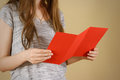Girl reading blank red flyer brochure. Read detailed booklet. Le Royalty Free Stock Photo