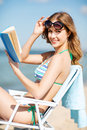 Girl reading book on the beach chair summer holidays and vacation Stock Photography