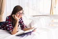Girl reading a book in bed, lying on her stomach smiling happy Royalty Free Stock Photo