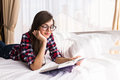 Girl reading a book in bed Royalty Free Stock Photo