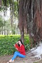 Girl reading the book. Blonde beautiful young woman with book sit under tree . Outdoor. Sunny day