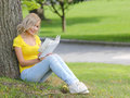 Girl reading the book. Blonde beautiful young woman with book sitting on the grass and leaning to the tree. Outdoor. Royalty Free Stock Photo