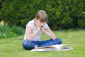 Girl reading a book in a garden beautiful astonished by Royalty Free Stock Photography