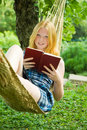 Girl reading book on hammoc Royalty Free Stock Photo