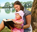 Girl reading book with her mother Stock Image