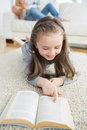 Girl reading book with her mother reading the newspaper on carpet Stock Photo