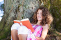Girl reading book while leaning on tree trunk happy teenage in park Royalty Free Stock Images