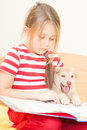 Girl reading book little with a puppy a Stock Photos