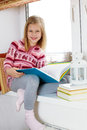 Girl reading a book little sitting on the windowsill in sweater and Royalty Free Stock Images