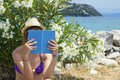 Girl reading a book in shade near the beach with rocks in background Royalty Free Stock Photography