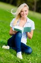 Girl reading book sits on the green grass in summer park Royalty Free Stock Images