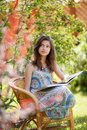 Girl reading book sitting in wicker chair outdoor Stock Images