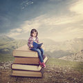 Girl reading a book on stack of books Royalty Free Stock Photography