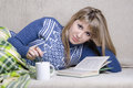 Girl reading a book under a blanket on the couch, and with a Cup of tea Royalty Free Stock Photo