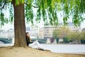 Girl reading a book under the tree in paris Stock Photos