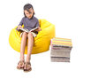 Girl reading books iii young malay asian a book on a yellow bean bag Royalty Free Stock Photo