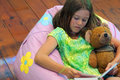 Girl reading cute little holding much loved teddy bear and book whilst reclining on bean bag Stock Image