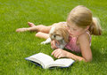 Girl reading with dog outdoors Royalty Free Stock Photo
