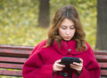 Girl reading ebook beautiful attractive cute caucasian young woman digital book sitting in a park by a autumn day with blurred Stock Photo