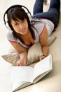 Girl reading and listening to music Stock Image