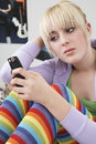 Girl reading text message on mobile phone beautiful teenage at home Stock Photos