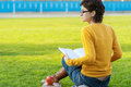 Girl reads book on lawn young beautiful woman in yellow sweater green field Royalty Free Stock Image