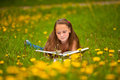 A girl reads a book in the meadow. Royalty Free Stock Photo