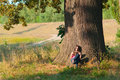 Girl reads the book under the huge oak