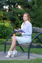 Girl ready to write with notebook sitting in park Stock Photography