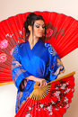 Girl with red asian fan Royalty Free Stock Image