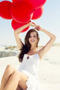 Girl with red ballons beautiful sitting in the beach Royalty Free Stock Photography