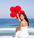 Girl with red ballons beautiful sitting in the beach Royalty Free Stock Photos