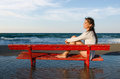Girl on a red bench portrait of beautiful sitting the beach Stock Photo