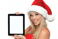 Girl in a red Christmas hat, holding tablet touch Stock Photo