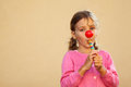 Girl with red clown nose sucks candies Stock Photo
