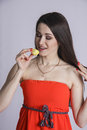 Girl in red dress eats yellow macaron diet concept brown haired woman delicious Stock Photo