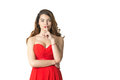 Girl in red dress holding a finger to his mouth