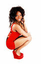 Girl in red dress a lovely jamaican young woman a short with her curly black hair crouching on the floor isolated on white Royalty Free Stock Photos