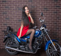 Girl in red dress on a motorcycle Royalty Free Stock Photo