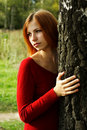 Girl in red dress snuggle up to tree Royalty Free Stock Photo